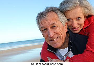 mulher, dar, passeio, piggyback, mar, homem sênior