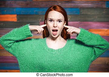 mulher, dela, cobertura, dedos, shouting, seu, orelhas
