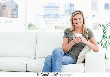 mulher, dela, copo, sentando, olhar, sofá, sorrizo, forward., mãos, lado