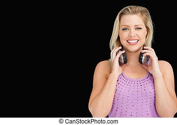mulher, dela, fones, atraente, segurando, sorrindo