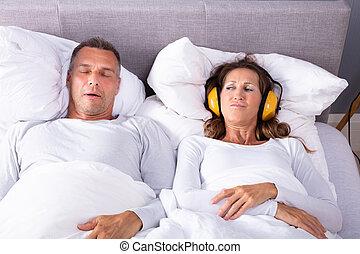 mulher, dela, orelhas covering, fones, enquanto, roncar, homem