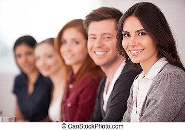 mulher, dela, sentando, câmera, pessoas, jovem, seminar., enquanto, outro, atraente, atrás de, sorrindo, fila