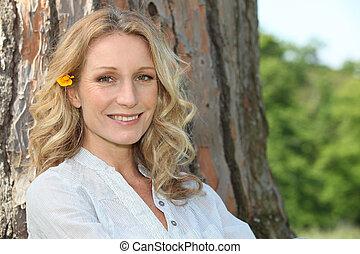 mulher, dela, sentando, summery, árvore, contra, cabelo, flor, tronco