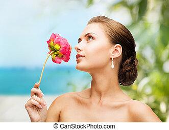 mulher, desgastar, brincos, e, cheirando, flor