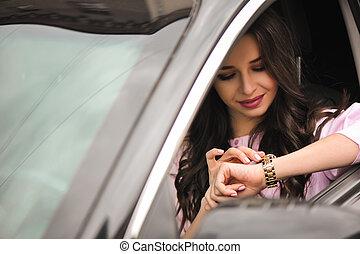 mulher, dirigindo um carro, e, olhando relógio