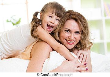 mulher, e, criança, menina, cama, tocando, e, sorrindo