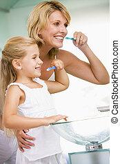 mulher, e, menina jovem, em, banheiro, dentes escovando