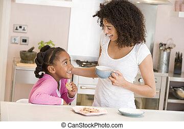 mulher, e, menina jovem, em, cozinha, com, biscoitos, e, café, sorrindo