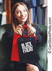 mulher, elegante, mostrando, sexta-feira, saco, pretas