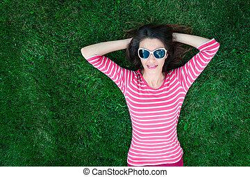 mulher, em, óculos de sol, mentir grama