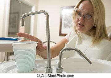 mulher, em, exame dental, sala, alcançar, água