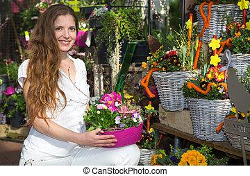 mulher, em, loja flor, entre, arranjos flor