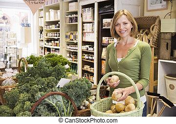 mulher, em, mercado, olhar, batatas, sorrindo