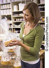 mulher, em, mercado, olhar, bolos, sorrindo