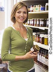 mulher, em, mercado, olhar, conservas, sorrindo