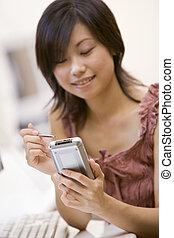 mulher, em, quarto computador, usando, assistente digital pessoal, sorrindo