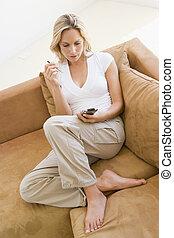 mulher, em, sala de estar, usando, assistente digital pessoal, sorrindo