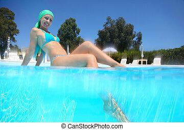 mulher, em, terno natação, senta-se, em, day-time, em, piscina, e, ponha, perna, em, água