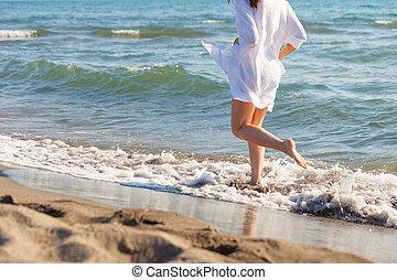 mulher, em, vestido branco, corrida, através, a, água, ligado, arenoso, mar, praia, ensolarado, dia verão, baixo órgão
