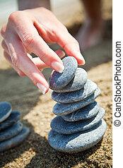 mulher, empilhando, pedras