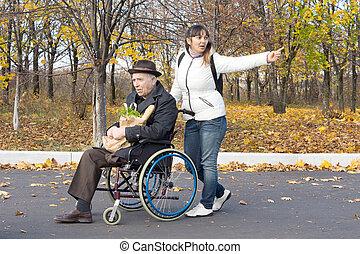 mulher, empurrar, um, homem idoso, em, um, cadeira rodas