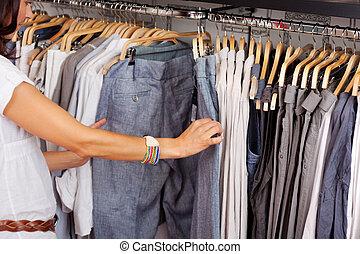 mulher, escolher, trouser, de, prateleira, em, loja roupa