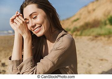 mulher, espantoso, praia., posar, mar, ao ar livre, sorrindo, agradado, feliz