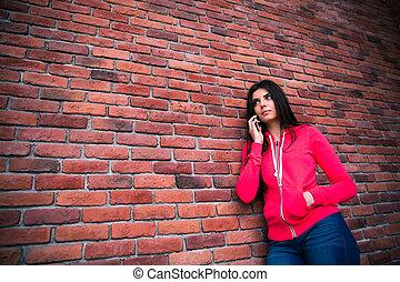 mulher, falando, parede, sobre, jovem, telefone, tijolo