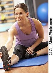 mulher, fazendo, esticar, exercícios, em, ginásio
