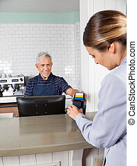 mulher, fazendo pagamento, através, mobilephone, em, contador