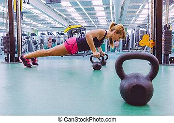 mulher, fazendo, pushups, sobre, kettlebells, em, crossfit, treinamento