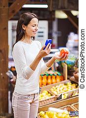 mulher feliz, com, smartphone, e, tomate, em, mercado
