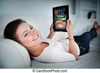 mulher feliz, mentir sofá, e, jogo, ligado, tabuleta