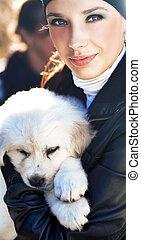 mulher, filhote cachorro, segurando, jovem