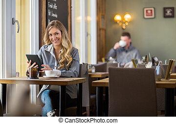mulher grávida, usando, tablete digital, em, coffeeshop