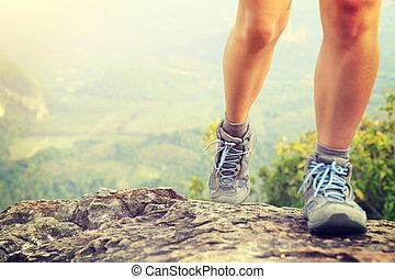 mulher, hiker, pernas, escalando, rocha, em, pico montanha