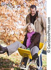 mulher homem, empurrando wheelbarrow