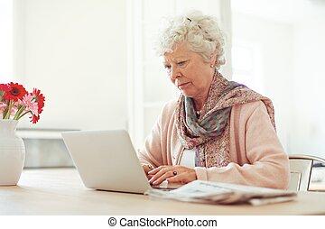 mulher idosa, digitando, algo