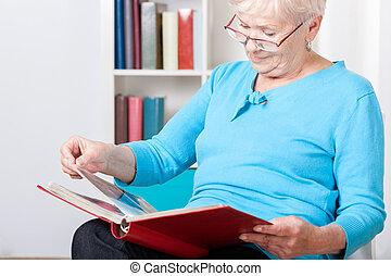mulher idosa, observar, fotografias