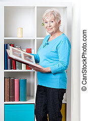 mulher idosa, olhando, álbum foto
