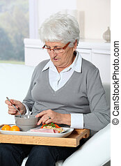mulher idosa, sentando, em, sofá, com, almoço, bandeja