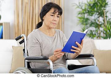 mulher inválida, cadeira rodas, livro
