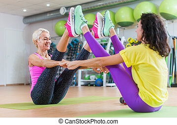 mulher, ioga, camarada, sentando, ginásio, pose, middle-aged, morena, trás, menina sorri, bote
