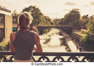 mulher jovem, admirar, a, pôr do sol, de, um, ponte
