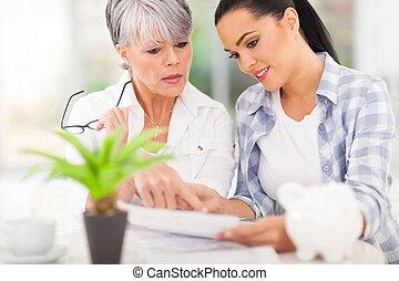 mulher jovem, ajudando, dela, mãe, notas pagando