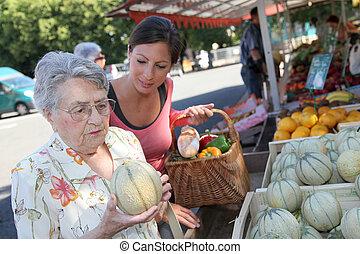 mulher jovem, ajudando, mulher idosa, com, shopping mantimento