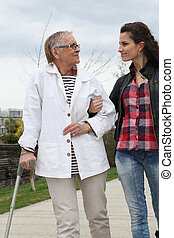 mulher jovem, ajudando, pessoa idosa, andar, com, um, muleta