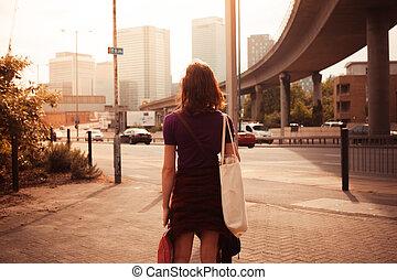 mulher jovem, andar, por, a, à margem estrada