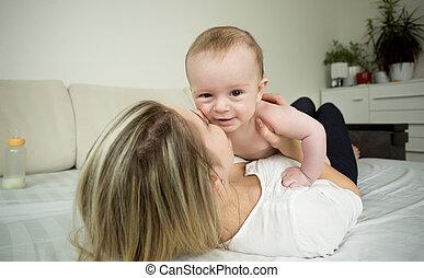 mulher, jovem, cama, bebê, retrato, sorrindo, tocando