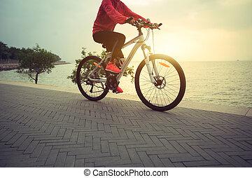 mulher jovem, ciclista, ciclismo, em, amanhecer, litoral